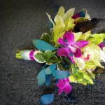Dramatic Orchid bridesmaid bouquet with peacock feathers.