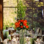 Exotic centerpiece of oversized orange flowers, green Bells of Ireland, and Tea Leaves. Fun and dramatic.