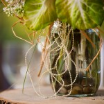 Strands of raffia and delicate pearls add rustic charm to Mason jar centerpieces.