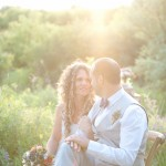 The sunset adds nostalgia and beauty to this shot of the wedding couple and their flowers.