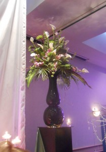 This dramatic floral arrangement looks modern and fresh atop an oversized black glass vase.