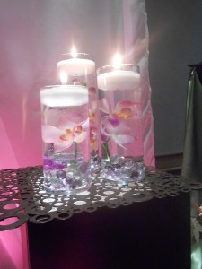 A collection of three cylinders with submerged orchids and floating candles.