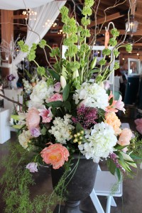 Oversized arrangement of Hydrangea, Bells of Ireland, and Curly Willow in pewter urn.