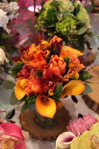 Full of lively colors and texture, this bouquet mixes bright oranges, deep burgandy, and rich greenery.