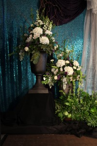Large urn arrangements in whites and fresh greens for the stage.