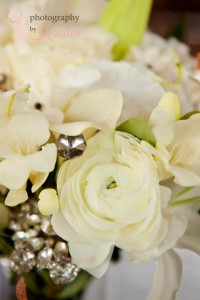 Beautiful all white bouquet of Lillies, Ranunculus, Freesia, and Garden Roses with crystal embellishments. Photo by: Photography by Kristen
