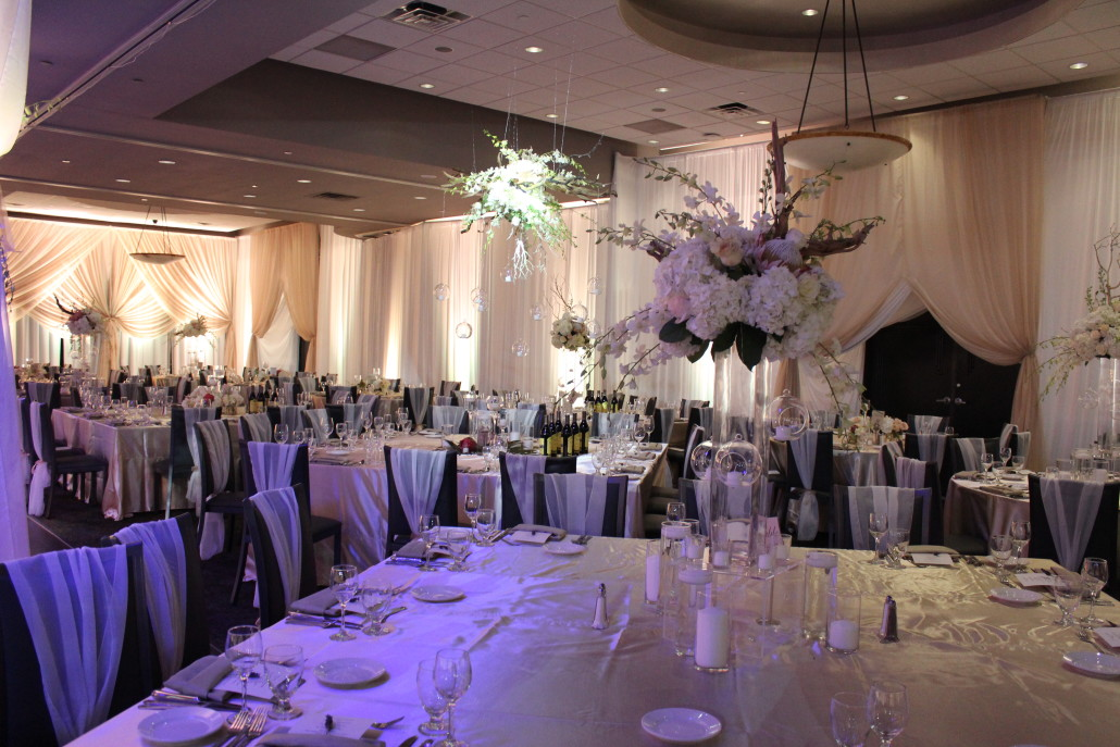 The design featured three styles of centerpieces. One style was a hanging centerpiece made of drift wood and ghost wood branches, dripping with white orchids and glass globes. Other styles accented this focal look with similar flowers and candles.